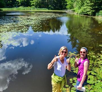 people posing outdoors near pond