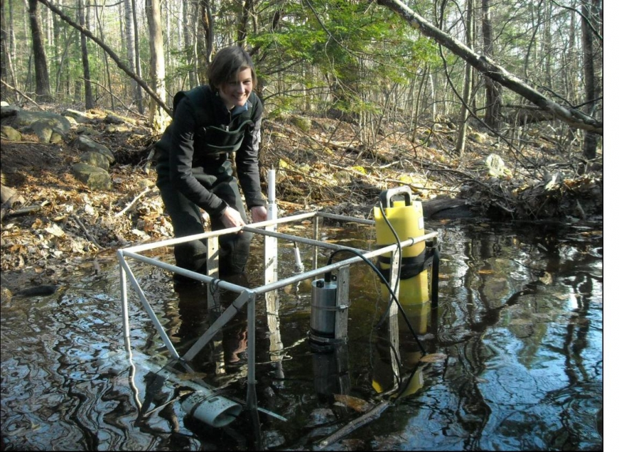 woman working in river with research equipment