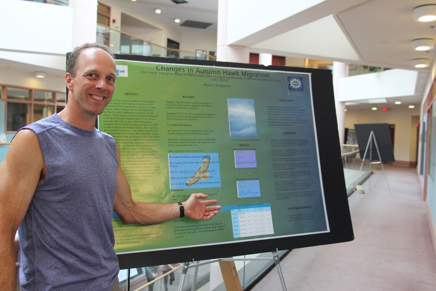 man presenting research poster