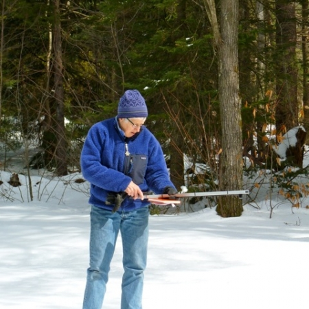 man outdoors in the snow with equipment