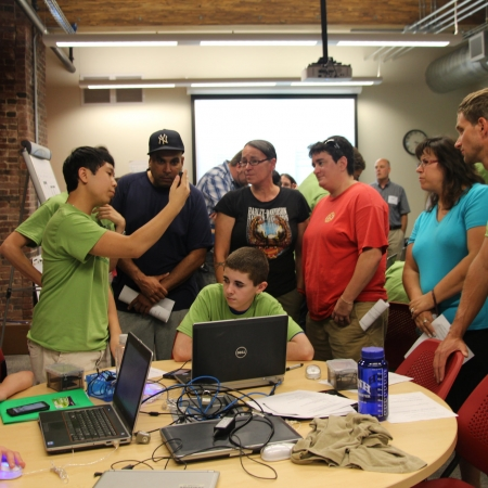 group of young people working together at computer