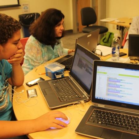 students sitting at tables looking at computer screens