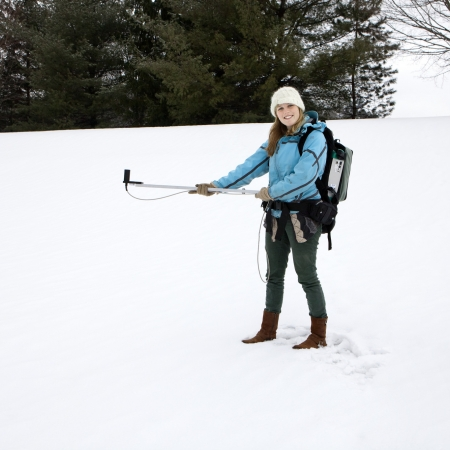 woman in the snow with research instrument