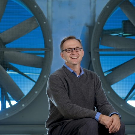 professor posing with large fans in background